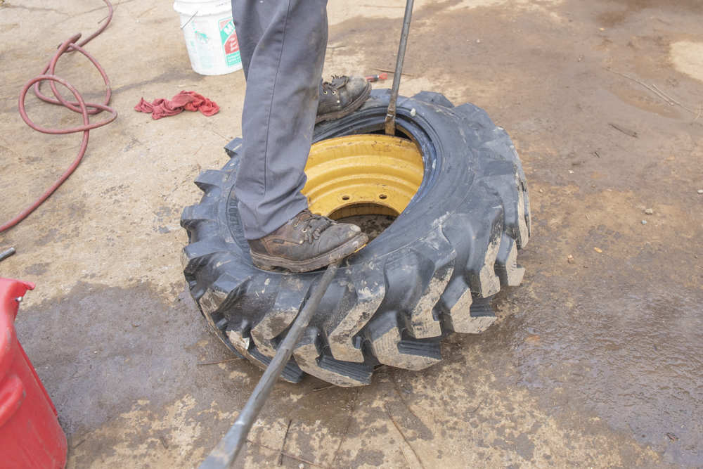 Continue pulling tire over flanges/side rings